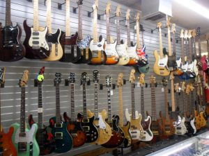Guitars line our walls in every shape, size , color, and style.